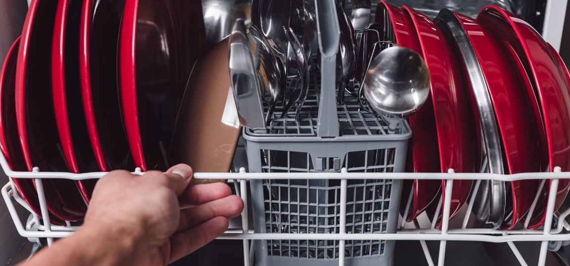 Man loading red plates into a dishwasher
