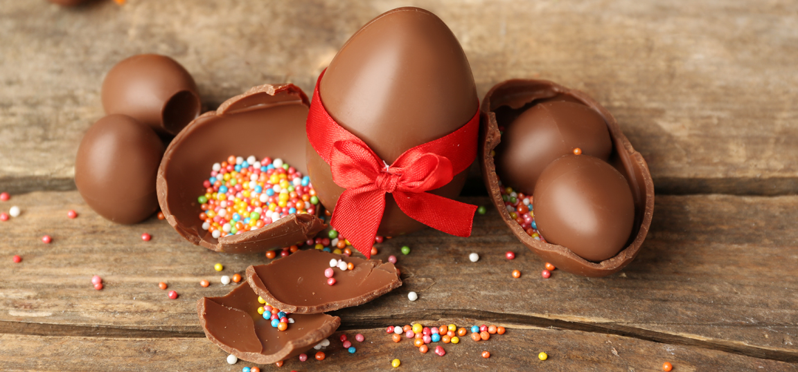 Egg full of small chocolate eggs with red ribbon