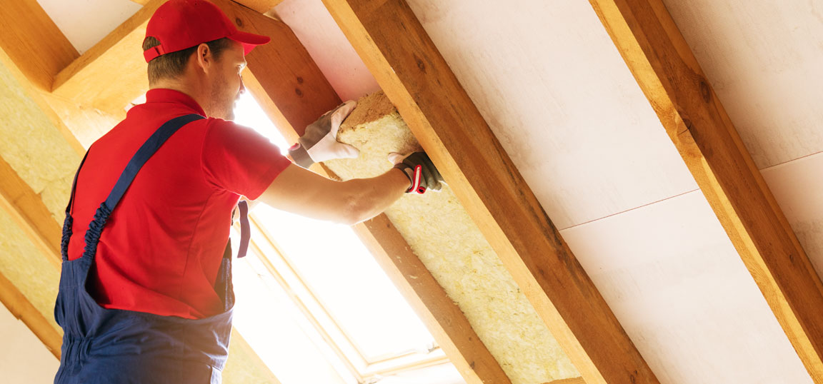 Man in red top and blue overalls fitting loft insulation to a home in the summer