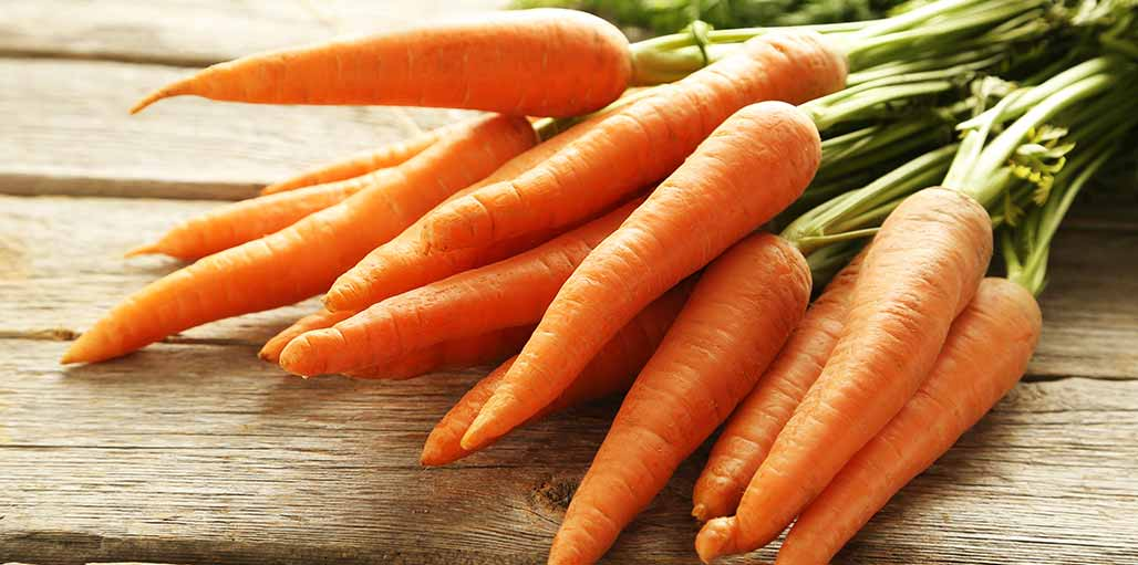 Bunch of carrots on a wooden worktop surface