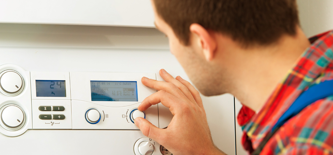 Man in red shirt near boiler, turning the temperature down on his heating system