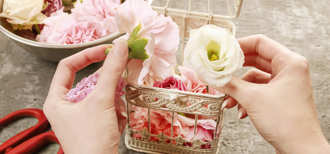 Woman arranging pink flowers in white cage with red scissors