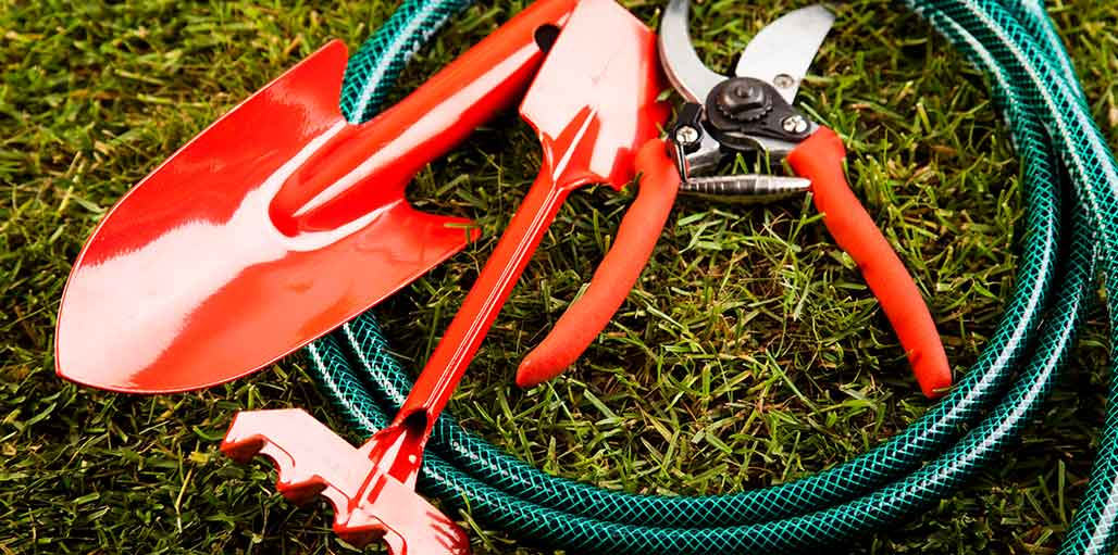 Image of red garden tools on hose on grass