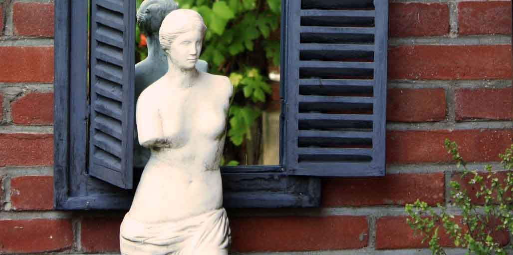 Statue in garden in-front of a garden mirror
