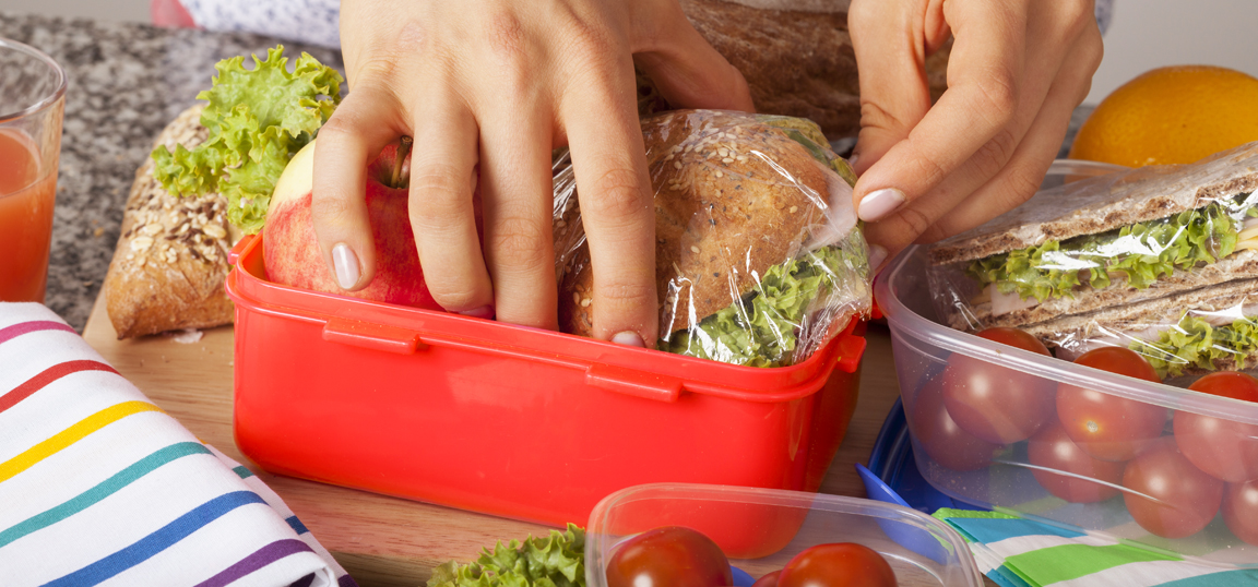 Woman putting wrapped ham and lettuce sandwich into a red lunch box with an apple surrounded by salad