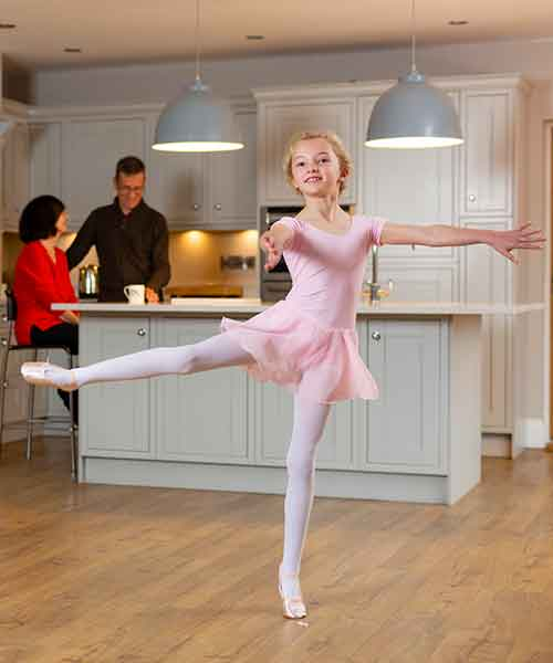 Girl performing ballet while parents chat in the kitchen while parents look on