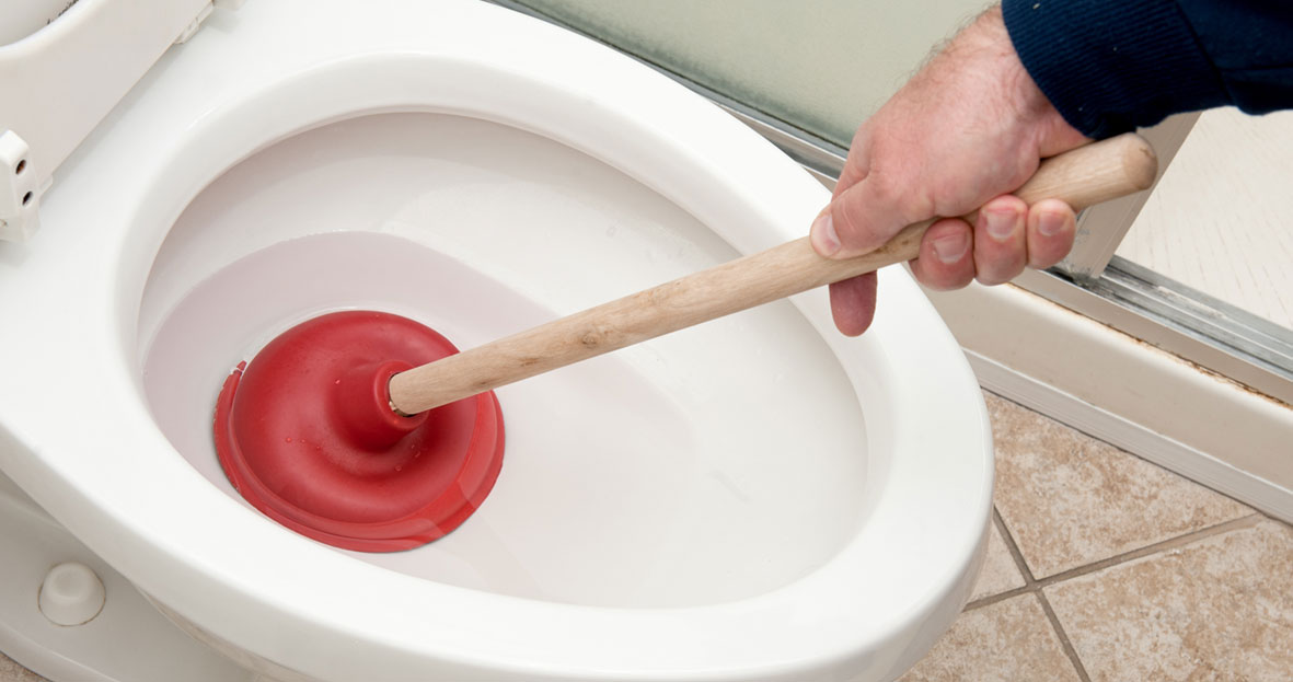 Man unblocking a toilet with a plunger
